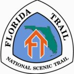 """Florida National Scenic Trail Logo features an orange """"FT"""" formed into what looks like a house in front of a green outline of the state of Florida and a blue background"""