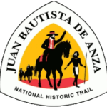 Triangular trail sign for the Juan Bautista de Anza NHT features a conquistador on a horse led by a Native guide against and yellow and red background