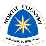 The North Country National Scenic Trail triangle-shaped sign logo features a yellow and white 8-pointed compass rose against a blue background.