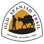 Old Spanish National Historic Trail triangle-shaped sign depicting a man leading a pack mule against a gold background
