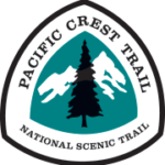 The Pacific Crest National Scenic Trail triangle sign logo features the silhouette of an evergreen tree against a green background with white mountains.