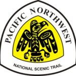 The Pacific Northwest Trail triangular sign logo features a black Native-American-style rendering of an eagle against a yellow background.