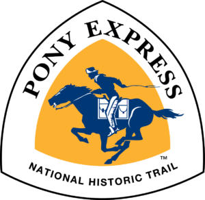 The Pony Express National Historic Trail triangle-shaped sign features and blue and white rider on horseback against a yellow background.