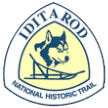 The triangular trail sign for the Iditarod National Historic Trail features a blue husky and sled against a yellow background