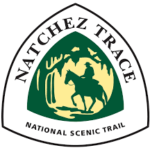 The Natchez Trace NST triangular sign features the silhouette of a man on horseback in a forest in dark green against a yellow background.