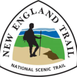 The New England National Scenic Trail triangular sign logo features the silhouette of a hiker in black on a brown cliff looking out over a green and blue valley.