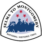 The Selma to Montgomery National Historic Trail triangle-shaped sign features the silhouettes of marchers in blue beneath three red stars.