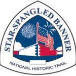 Star-spangled Banner National Historic Trail triangle-shaped sign featuring an image of Fort McHenry with a U.S. Flag and fireworks overhead