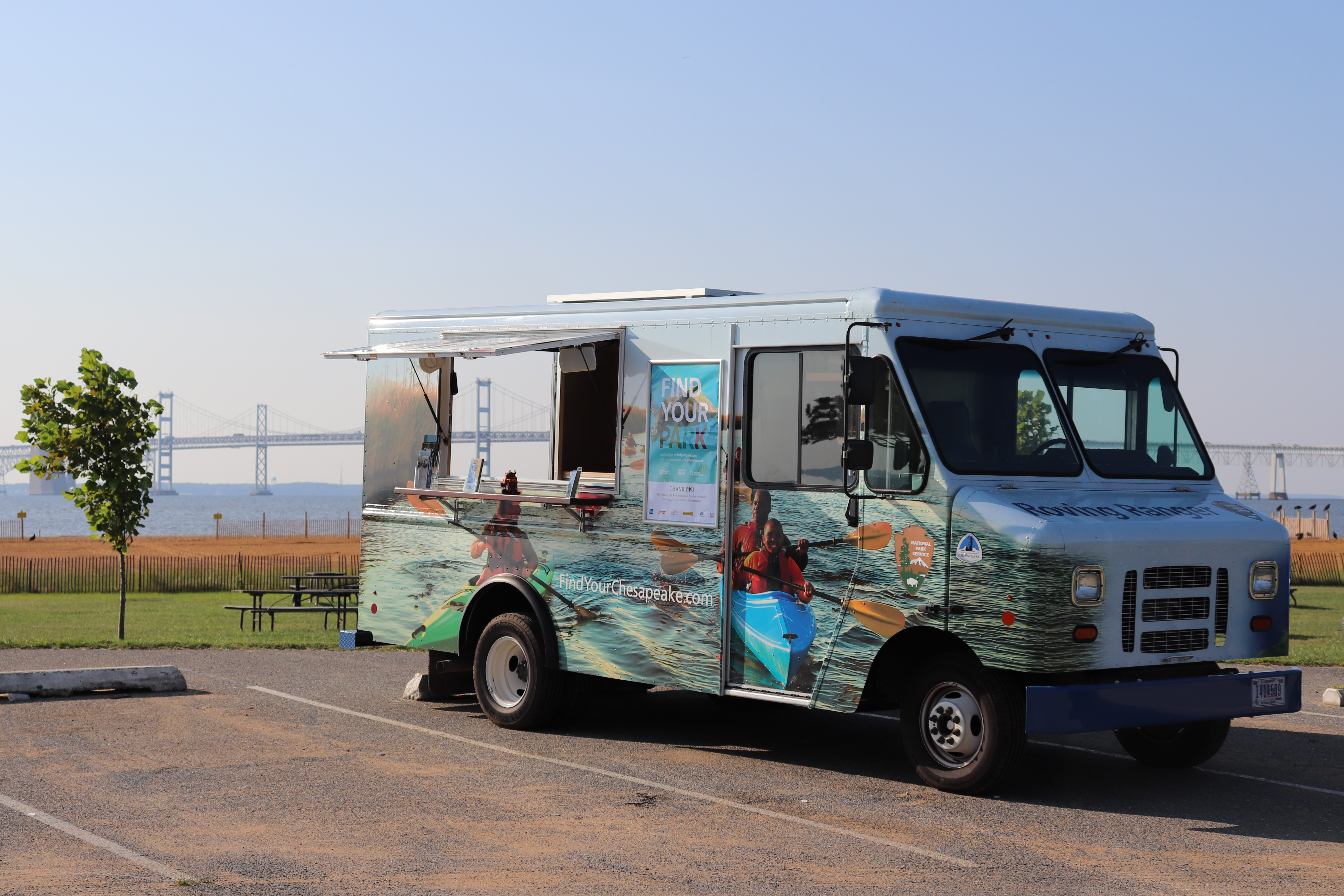 Chesapeake Roving Ranger van parked in front of a park with the waters of the Chesapeake Bay in the distant background. The van features a colorful vinyl wrap depicting kayakers on the water trail.