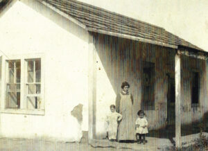 A woman stands outside the Trujillo Adobe with a young boy and girl near the beginning of the 20th Century.