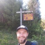 Chase Gregory poses for a selfie in front of a Finger Lakes Trail Sign