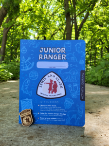 Close up photo of the blue Lewis and Clark Junior Ranger booklet with a Junior Ranger badge propped in front of it.