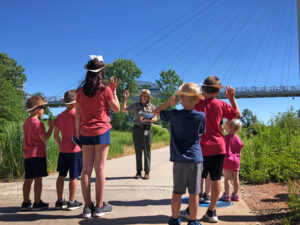 A National Park Service Ranger raises her hand in front of six children -- 5 in pink t-shirts, one in a blue t-shirt -- who are also raising their hands. There is a bridge in the background.