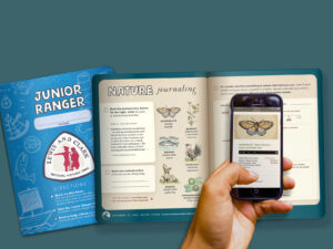 A phone scans a photo of a butterfly inside the Junior Ranger booklet.