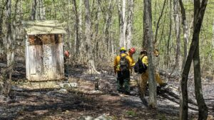 Firefighters examine the damage to a tent platform caused by the East Mountain Fire.